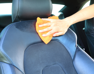 Mans Hand Cleans A Leather Car Seat